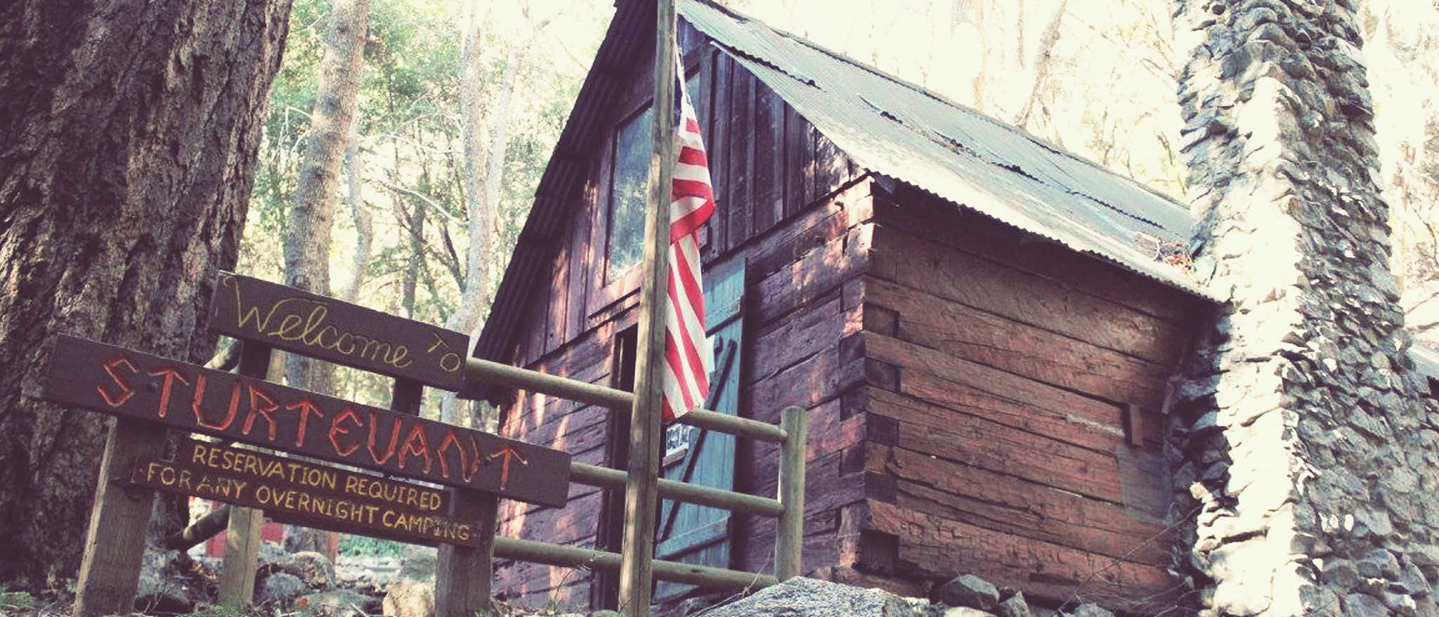 Picture the Sturtevant Camp ranger cabin with U.S. flag and sign welcoming visitors.